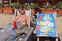 Sunny Beach, Nesebar, Bulgaria..A young holidaymaker asleep in the morning on Sunny Beach, the largest holiday resort in the Balkans, and a popular destination for cheap foreign package tours.