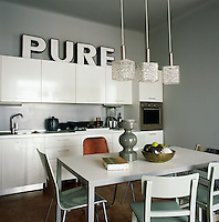 The kitchen/diner has a retro feel with walls and furniture painted in a soft grey. The simple table and chairs in the centre of the room provide informal dining