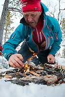 Saltoluokta Mountain Station, Jokkmokk, Lapland, Sweden, March 2013. Claes Jorgen carefully builds a fire on the snow. Arctic survival training and winter bushcraft  in the frigid mountains of the Stora Sjofallet National Park and Sarek National Park with mountain guide Claes Jorgen Pohl.  Photo by Frits Meyst/Adventure4ever.com