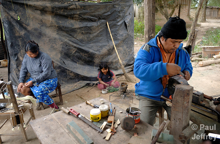 Jose Luis Fernandez (r) and his wife, Graciela Sarabia (l), an indigenous couple, work at artisan jewelry in their home in Embarcacion, Argentina, while their daughter Ana Fernandez, 4 years old, plays in the background.