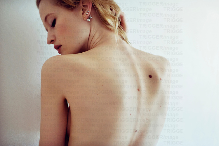 Portrait of young naked woman with pierced ears looking down her shoulder with her back turned to the camera