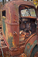 View of the cab of an abandoned rusted truck in the woods in rural West Virginia mountains. The door is open and the inside of the cab is visible