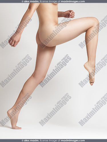 Dynamic photo of a young naked woman gracefully leaping forward