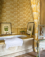 Golden yellow toile de Jouy wallpaper and matching curtain bring a touch of 18th century luxury to this bathroom alcove