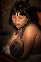 Viriunaveteri, Venezuela. Yanomami family inside a hut..The village of Viriunaveteri consists of 15 huts around a muddy square. It's situated in the Venezuelan Amazone several days by boat from the nearest town. This community on the banks of the Casiquiare is one of the few Yanomami villages that actually has some contact with the outside world. Most other tribes live deeper in the jungle.