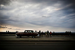 Dark clouds loom over the Gulf of Mexico as Cubans hang out along the Malécon, in Havana, Cuba, on Sunday, April 27, 2008. The Malécon is one of the most popular spots for Cubans on weekends.