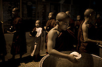 A novice monk serves rice to other monks at a monastery on the outskirts of Mandalay, where some 2,300 monks live and study.