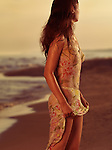 Young woman in wet summer dress on a beach at sunset