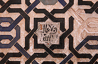 Detail of stucco work with interlacing pattern and Arabic script, in the Patio of the Gilded Room, between the Mexuar and the Gilded Room or Cuarto Dorado in the Comares Palace, Alhambra Palace, Granada, Andalusia, Southern Spain. It was built under Mohammed V in the 14th century. The Alhambra was begun in the 11th century as a castle, and in the 13th and 14th centuries served as the royal palace of the Nasrid sultans. The huge complex contains the Alcazaba, Nasrid palaces, gardens and Generalife. Granada was listed as a UNESCO World Heritage Site in 1984. Picture by Manuel Cohen