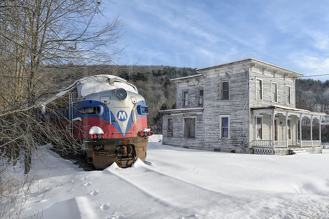 Abandoned railroad locomotives have finally met their deadline and sit beside a snowed-in creepy house...not a soul around and only one set of footprints in the snow...