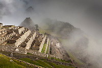 """Morning fog and clouds reveal Machu Picchu, the ancient """"lost city of the Incas"""", 1400 CA, 2400 meters. Discovered by Hiram Bingham in 1911. One of Peru's top tourist destinations."""