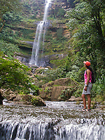 A hiker crosses a stream near a waerfall in San Gil - Colombia