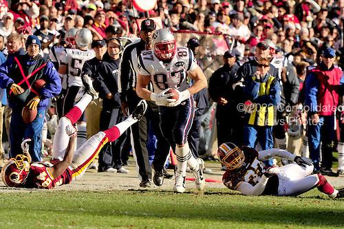 New England Patriots tight end Rob Gronkowski (87) leaves  Washington Redskins defenders DeJon Gomes (24) Reed Doughty (37) in his wake as he carries for a 49 yard gain in the first quarter at FedEx Field in Landover, Maryland on Sunday December 11, 2011..Credit: Ron Sachs / CNP.(RESTRICTION: NO New York or New Jersey Newspapers or newspapers within a 75 mile radius of New York City)