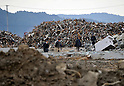 March 11, 2012, Rikuzentakata, Japan ? People are dwarfed by mountains of debris, remnants from the devastating earthquake and tsunami, in Rikuzentakata, Iuwate Prefecture, some 402 km northeat of Tokyo, on Sunday, March 11, 2012..Memorial ceremonies were held throughout Japan to mark the one year anniversary of the massive earthquake and tsunami that struck the country?fs northeastern region, killing just over 19,000 people and unleashing the world?fs worst nuclear crisis in a quarter century. The quake was the strongest recorded in the nation?fs history, and set off a tsunami that towered more than 65 feet in some spots along the northeastern coast, destroying thousands of homes and wreaking widespread destruction. (Photo by Natsuki Sakai/AFLO) AYF -mis-