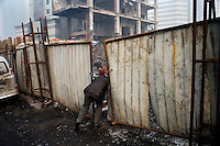 Construction workers enter a work site in Urumqi, Xinjiang, China.