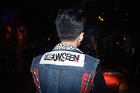 Zhou Ge, second singer for the Chinese psychobilly band the Angry Jerks, waits for a concert to start at Castle Bar in Nanjing, China.  Zhou Ge is wearing a home-made denim vest with a patch for the band The Unseen on the back.