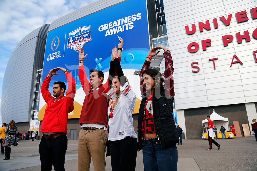 Ohio State Buckeye fans, left to right, Jeff Lonchir, Mike Lee, Geri Siudzinski, and Rachel Lonchor do the O-H-I-O in front of the stadium prior to the College Football Playoff semifinal Fiesta Bowl against the Clemson Tigers at University of Phoenix Stadium in Glendale, Arizona on Dec. 31, 2016.