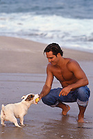 Man playing ball with a Jack Russell at the ocean in California