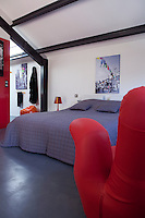 The metal beams and concrete floors are testimony to the original function of the house and are softened by a quilted bedcover and curved armchair in the shape of a hand