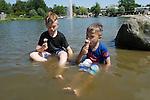 Foto VidiPhoto<br /> <br /> DALEM &ndash; Het is de ultieme verkoeling woensdag: met je kleren aan en een ijsje in je mond in een zwemplas. De broertjes Owen (9) en Quinn van der Meulen (5) uit Leeuwarden spelen onder toeziend oog van oma en opa woensdag in een waterplas bij het Drentse Dalem. Nederland trok tijdens de tropische temperaturen van ruim boven de 30 graden massaal naar zwembaden en waterplassen om hoofd en lichaam te verkoelen. Woensdag was de eerste offici&euml;le tropische dag van het jaar, waarbij de hoogste temperaturen in Drenthe werden bereikt. Zelfs op de Waddeneilanden was het met 27 graden ongebruikelijk warm.