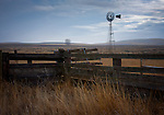 Washington, Davenport. A windmill and fence on the farmlands in Eastern Washington.