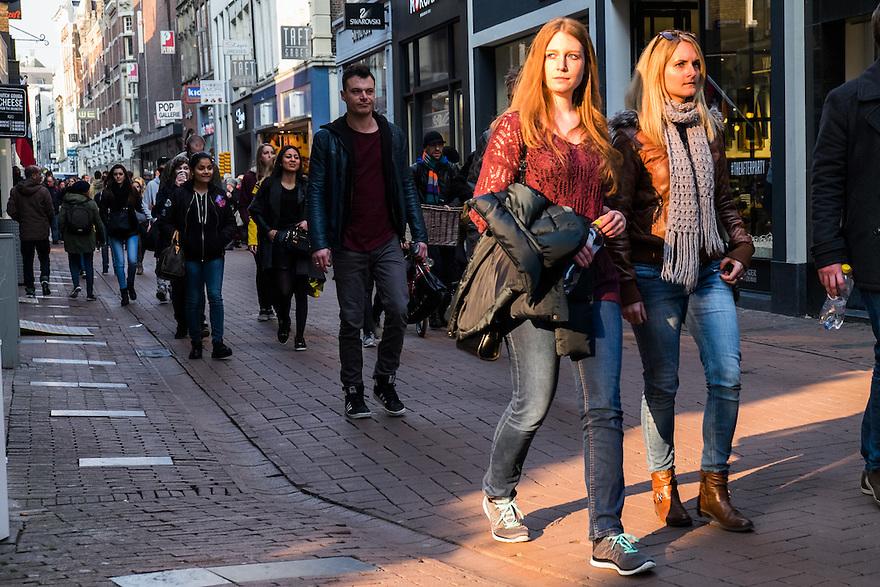 Nederland, Amsterdam, 19 maart 2015<br /> Kalverstraat, Amsterdam. Een streep laat zonlicht vangt winkelende mensen. <br /> Foto: Michiel Wijnbergh