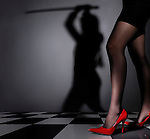Young sexy woman legs in the foreground and her shadow with a sword in the background. Appearances are deceptive concept.
