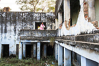 Santwana Manju of Guria looks around the deserted building of one of the largest of the ten brothels that Guria had raided and seized in the Shivdaspur red light area in 2005 rescuing 57 underaged girls, and jailing 39 perpetrators, in Varanasi, Uttar Pradesh, India on 22 November 2013. The facade of the building is minimalistic and unsuspicious, but the rear of the building opens into a sprawling honeycomb of cubicles both on ground level and underground.