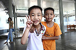 "A boy flashes a peace sign at the Duc Son Pagoda orphanage in Hue, Vietnam. The facility is currently home to 170 children. Relying solely on donations, the nuns who run the orphanage have sent 140 children to university or vocational school since they opened its doors in 1987. ""Only love can make the world warmer and more peaceful,"" its director says. April 22, 2013."