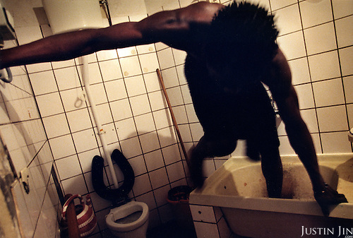 An illegal immigrant from Sierra Leone gets out of a bath-tub in a safe-house Amsterdam's Bijlmer area. .Picture taken 2002 by Justin Jin. ..