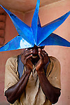 A man wears a paper star, found in the rubble of a former school, as a hat for a joke on July 7, 2010 in Port-au-Prince, Haiti.