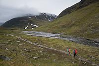 Group of hiker hiking along rocky trail through mountain landscape of Tjäktjavagge valley, near Sälka hut, Kungsleden trail, Lapland, Sweden