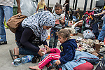 A mother helps find shoes for her daughter at a makeshift refugee camp at the Budapest Keleti railway station.<br /> <br /> Hundreds of refugees from mostly Syria and Afghanistan gather at the Budapest Keleti railway station waiting for trains to leave for destinations such as Austria, Germany and Sweden, in Budapest, Hungary, on Tuesday, Sept. 8, 2015. Hungary's Prime Minister Viktor Orban created an anti-refugee campaign to generate hate against those fleeing war in their home countries. The country is currently 50% xenophobic and the government has become increasingly authoritarian.