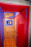 A walk-in shower is lined in warm ochre tiles and painted vibrant shades of purple and red with a pair of small mirrors framed in mosaic and antique tiles