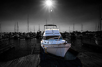 A boat, moored at the San Leandro Marina, against a  black and white background, thanks to Photoshop, of sailboats, all under a late afternoon sunburst.