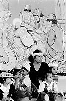 Republic of Nauru. Central Pacific. Nauru is a tiny island (21 square-km). Family gathering on a hat parade during Easter week. A  mother and her children sit on the concrete ground near a wall where the painting represents a religious scene. The Virgin Mary and the Three Magi (the Three Wise Men) kneel before the the coffin of infant Jesus Christ. © 1999 Didier Ruef