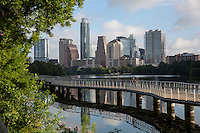 Perfect time for a bike ride during this gorgeous view of early morning sunrise on the Boardwalk Trail on Lady Bird Lake overlooking the downtown Austin Skyline - Stock Image.