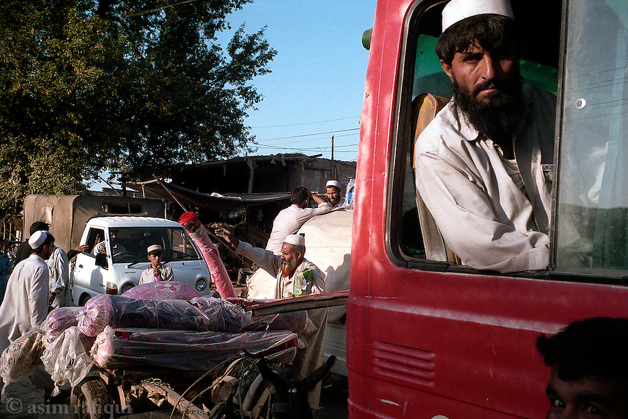 Scene outside the Shamshatoo refugee camp for Afghan refugees.  Traders load up to take goods to the main markets of Peshawar while others wait for their transports to take them to jobs in the city.  Hundreds of thousands of Afghanis continue to live and conduct their businesses in Pakistan.