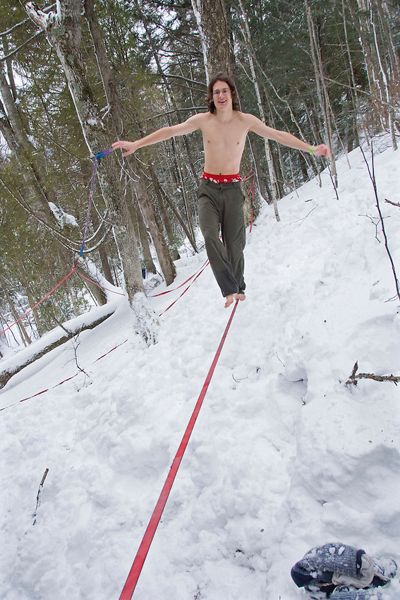 A shirtless man practices agility on a slack line during the Michigan Ice Fest at Pictured Rocks National Lakeshore in Munising Michigan Upper Peninsula.