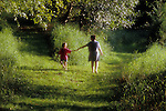 Mother and daughter ( 6 years old) walking on a grassy path coming to a crossroad in path  Lake Pleasant Bothell Washington State USA MR