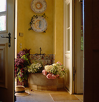 Freshly cut flowers have been placed in a stone basin in this entrance hall