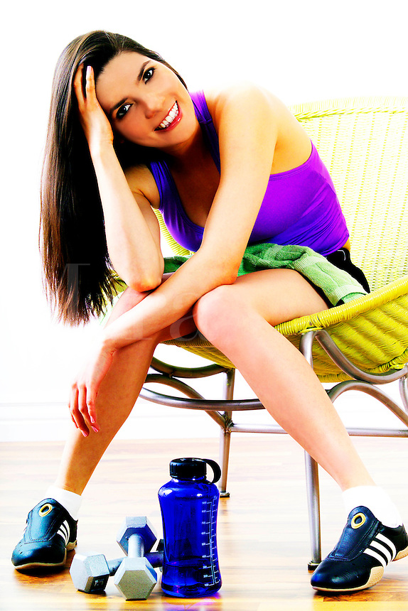 Beautiful female sitting with water bottle and weights after her workout.