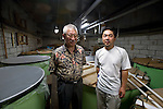 "Shinrokurou Amae and chief brewer Kazuhiro Ueno pose inside the kura of Nakayu Sake Brewery in Kami Town, Miyagi Prefecture,  Japan on 02 Sept. 2012. Amae and Sendai farmer Kazuyoshi Otomo cleaned up Otomo's rice that had been affected by the March 2011 tsunamis and joined forces to make a ""Recovery Sake,"" the recipe for which was created by Ueno. Photographer: Robert Gilhooly"
