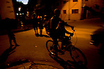 Cuban boys ride through streets at night.
