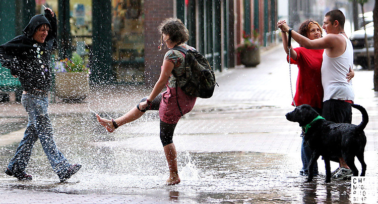 From left, Raven, did not provide last name, Jennaveave Edmondson, Talya Hernandez, Andrew Phillips and Damon the black lab enjoy the afternoon shower in Old Town Fort Collins on Wednesday, July 2, 2008.