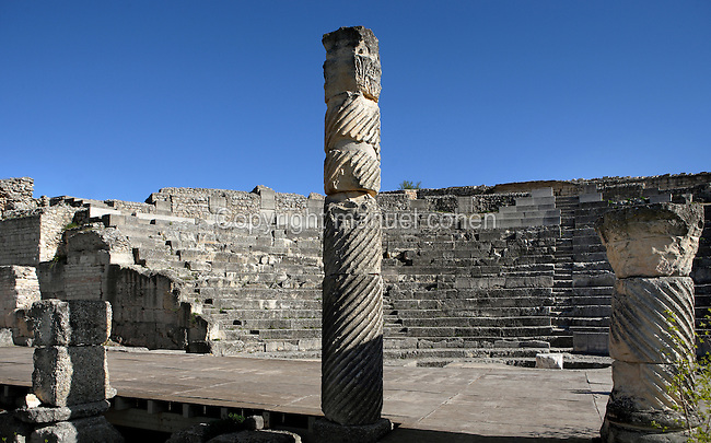 Low angle view of Theatre, c. 40-60 AD, Segobriga, Spain, pictured on April 13, 2006, in the afternoon, with columns in the foreground. Seating 2,000 people, the raked auditorium surrounds a semi-circular stage. The theatre was decorated with ornate columns and statues whose ruins remain. Segobriga was founded by the Romans in the 1st century BC, after the Punic wars, and the town was developed during the reign of  Augustus. It became an important administrative centre whose local industry was mining 'specularis lapis', a crystallized sheet gypsum used for window glass. Picture by Manuel Cohen.
