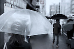 Out of focus photo of people with umbrellas walking on streets of Tokyo, Japan