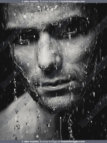 Man face wet from water pouring on it, artistic dramatic black and white portrait.
