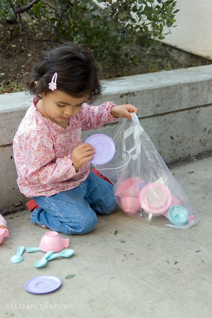 Berkeley CA Girl, two and a half, half Nepalese, cleaning up her tea set at the end of her play MR