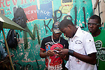 Men play with their mobile phones amid market stalls on July 8, 2010 in Port-au-Prince, Haiti.